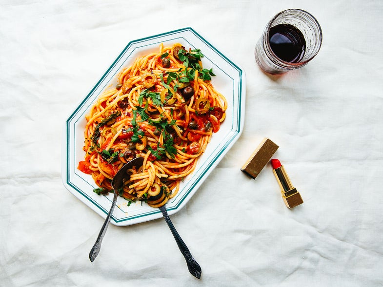 plate of pasta puttanesca and a glass of red wine