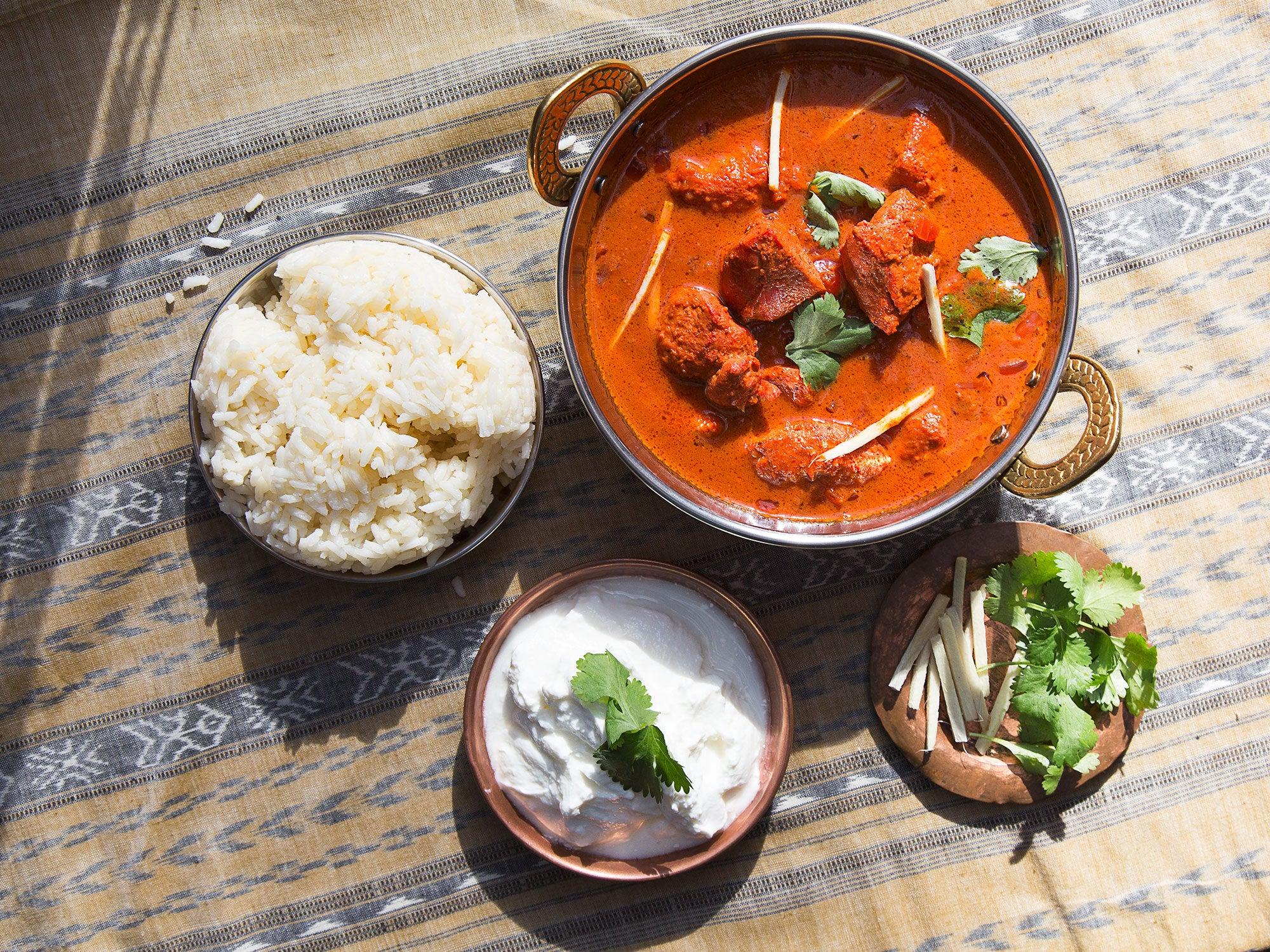 bowl of chicken tikka masala with rice and yogurt