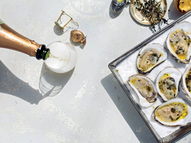Grilled Oysters on a Bed of Salt with a bottle of Champagne