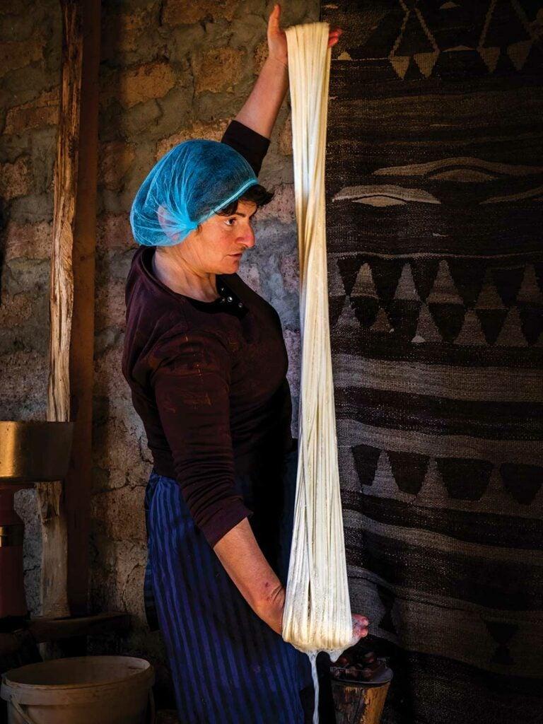 cheesemaker stretches warm curds