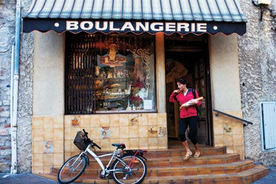 A woman pauses for her daily bread at Boulangerie La Belle Epoque in Antibes.