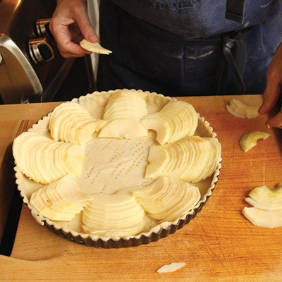 Working with one row at a time, she slides a metal spatula under half the row and transfers it to an unbaked tart shell