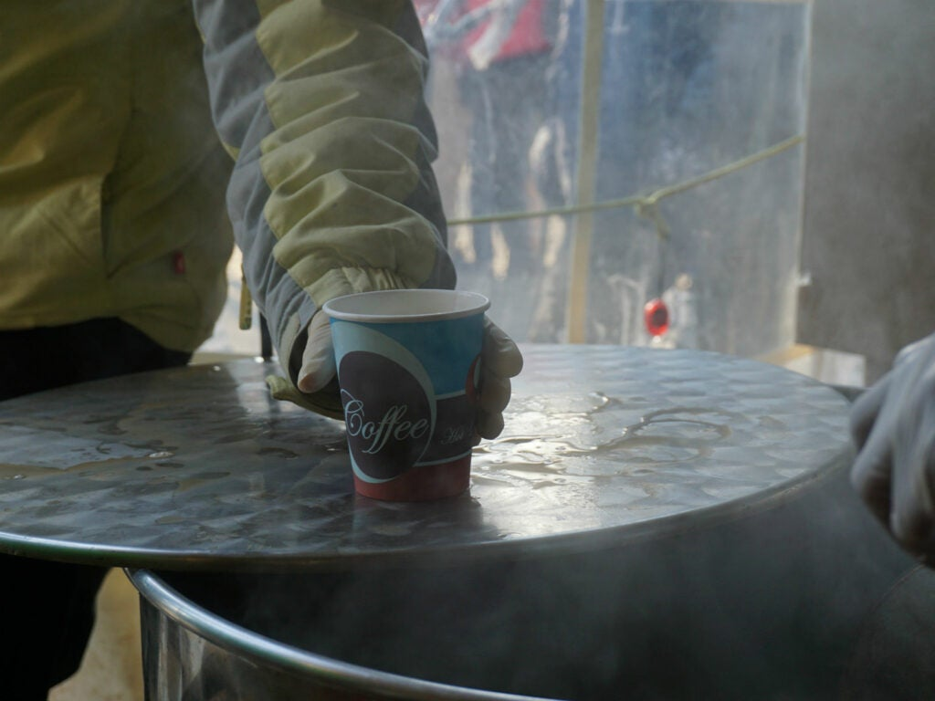 A volunteer serves a cup of tea out of one of the tubs