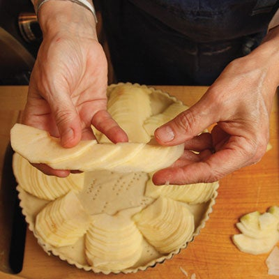 She then takes six or seven slices from the remaining apple and spreads them out lengthwise to form a narrow row of overlapping slices, which she arranges in an arc in the tart shell