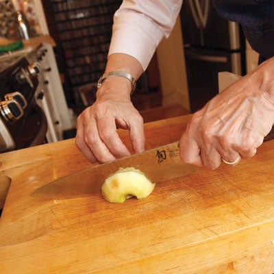 Working with one apple half at a time, she makes thin crosswise slices, keeping the heel of her knife slightly above the cutting board with each downstroke so the slices remain connected at one end