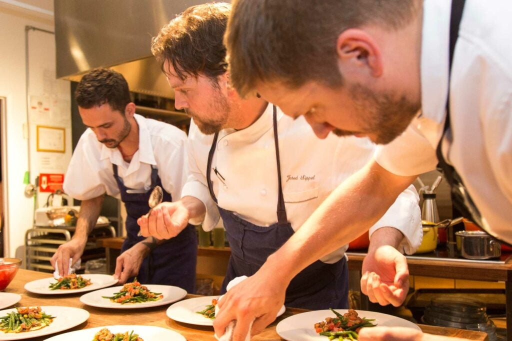 Chef Jared SIppel (center) puts the finishing touches on a salad with his team