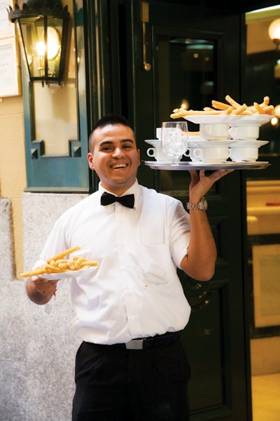 A server in Madrid, Spain, carries hot chocolate and churros