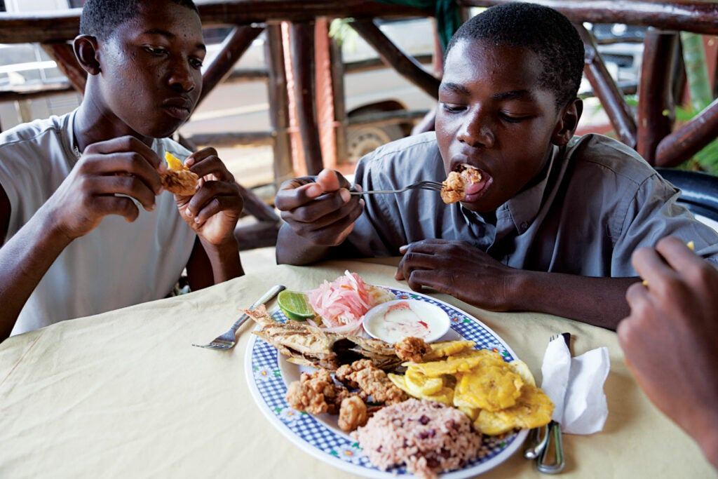 Boys enjoy a lunch of fried conch, kingfish, plantains, and rice and beans with coconut milk at Restaurante Corozal, in Corozal, Honduras