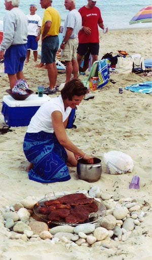 woman grilling on the beach