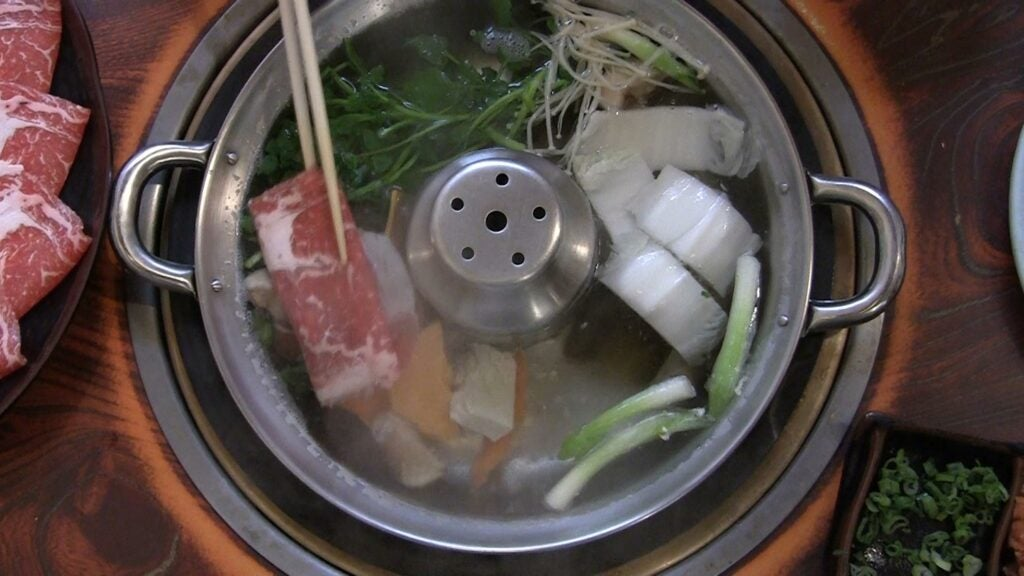 A piece of beef swishes through the hot water and vegetables.
