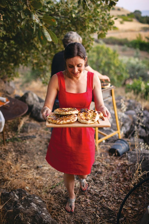 Lisa Fisher carries a tray of grilled pita