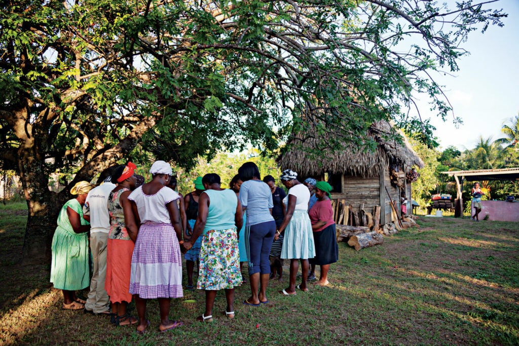 Members of a cassava bread producing cooperative share a prayer in Ciriboya, Honduras