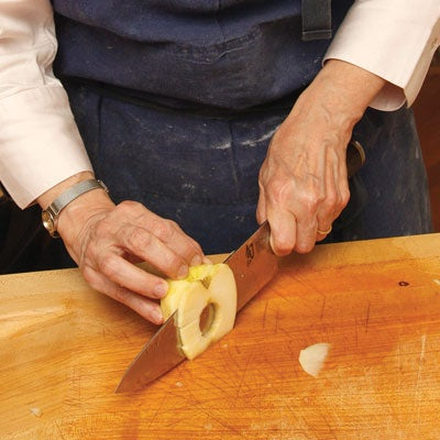 She trims the bud and stem ends, then stands the apple half on end to cut a thin layer from the cored side so that the slices fully separate but remain stacked together