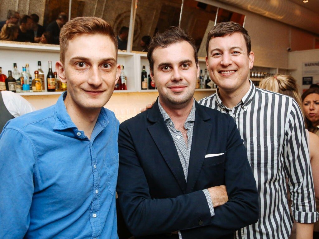 Chris Cohen of SAVEUR, writer Mark Byrne, and Andrew Richdale of SAVEUR pose in front of the bar at Fusco.