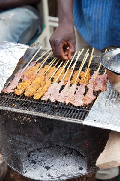 A street vendor grills kabobs