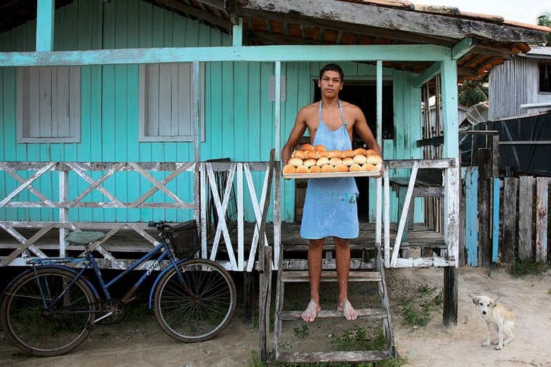 Luciano Lima holds a tray of just-baked rolls at a bakery in the village of Pesqueiro, near Soure.