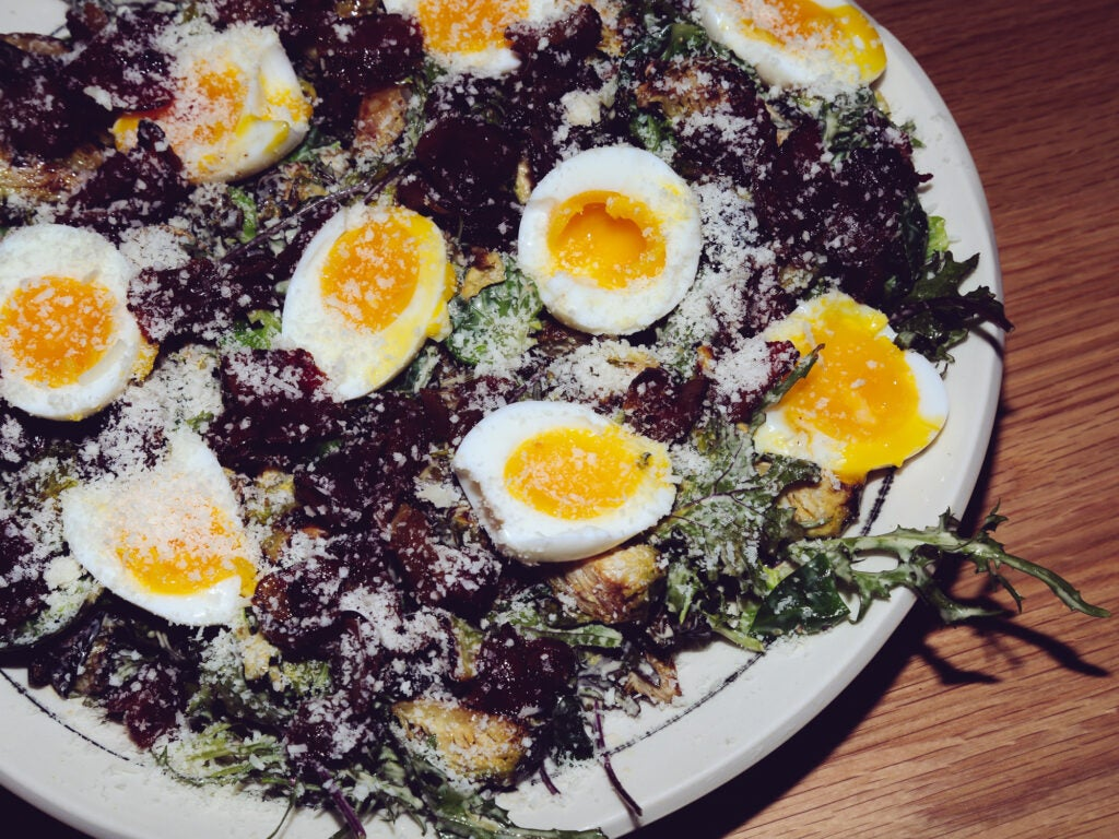 Caesar salad is always better when topped with brussels sprouts, bacon, and some soft eggs
