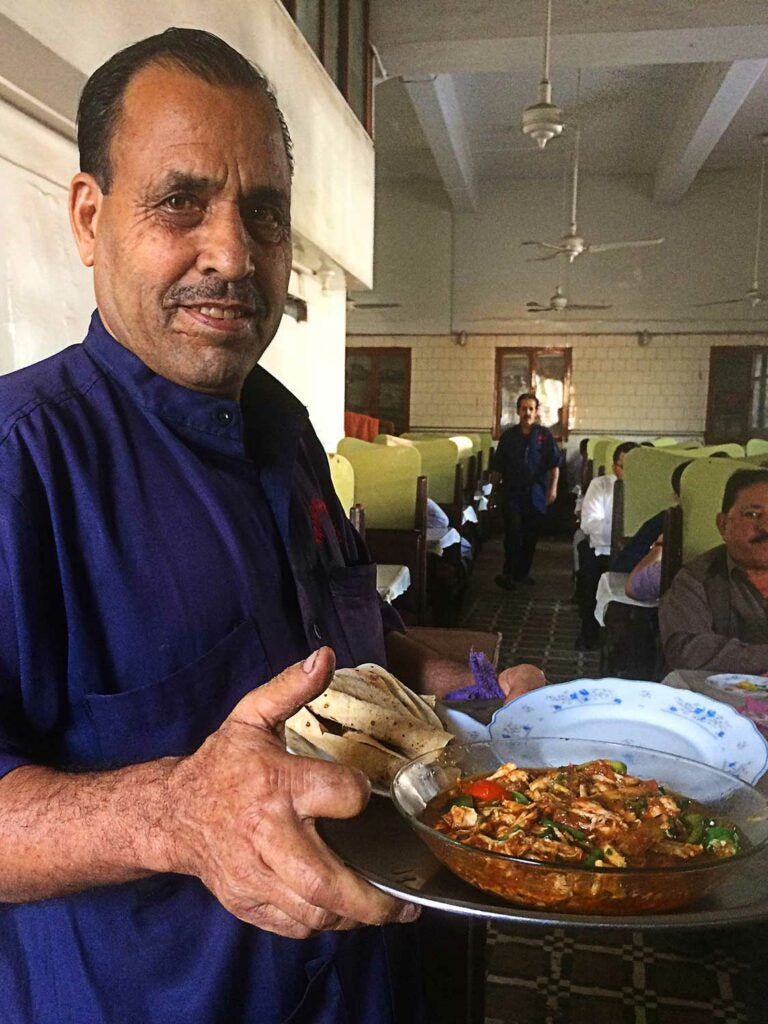 A server at Khairabad carries a platter of ginger chicken and roti.