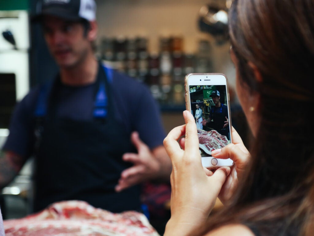A blogger takes a photo during the Fleisher's butcher demonstration on Tuesday.