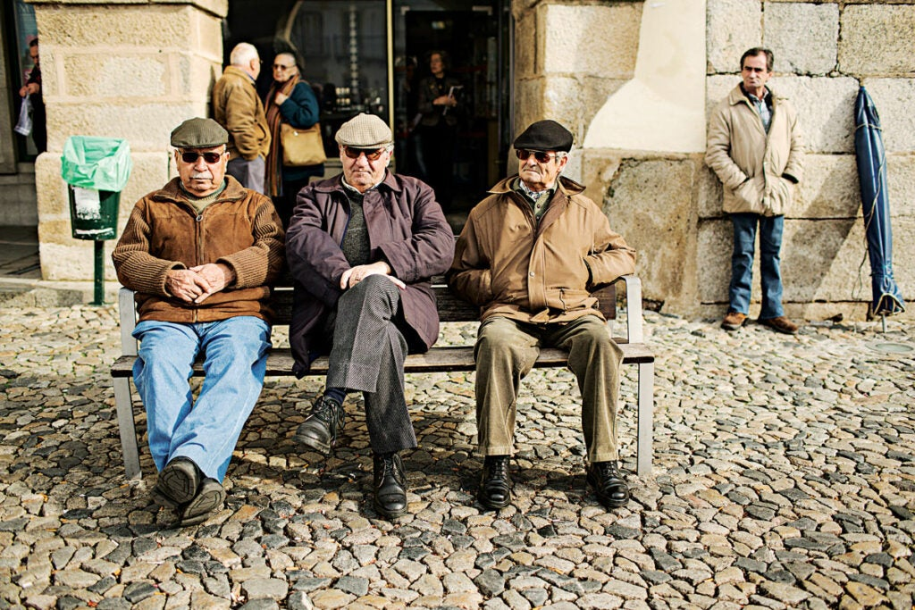 group of older men sitting on a bench