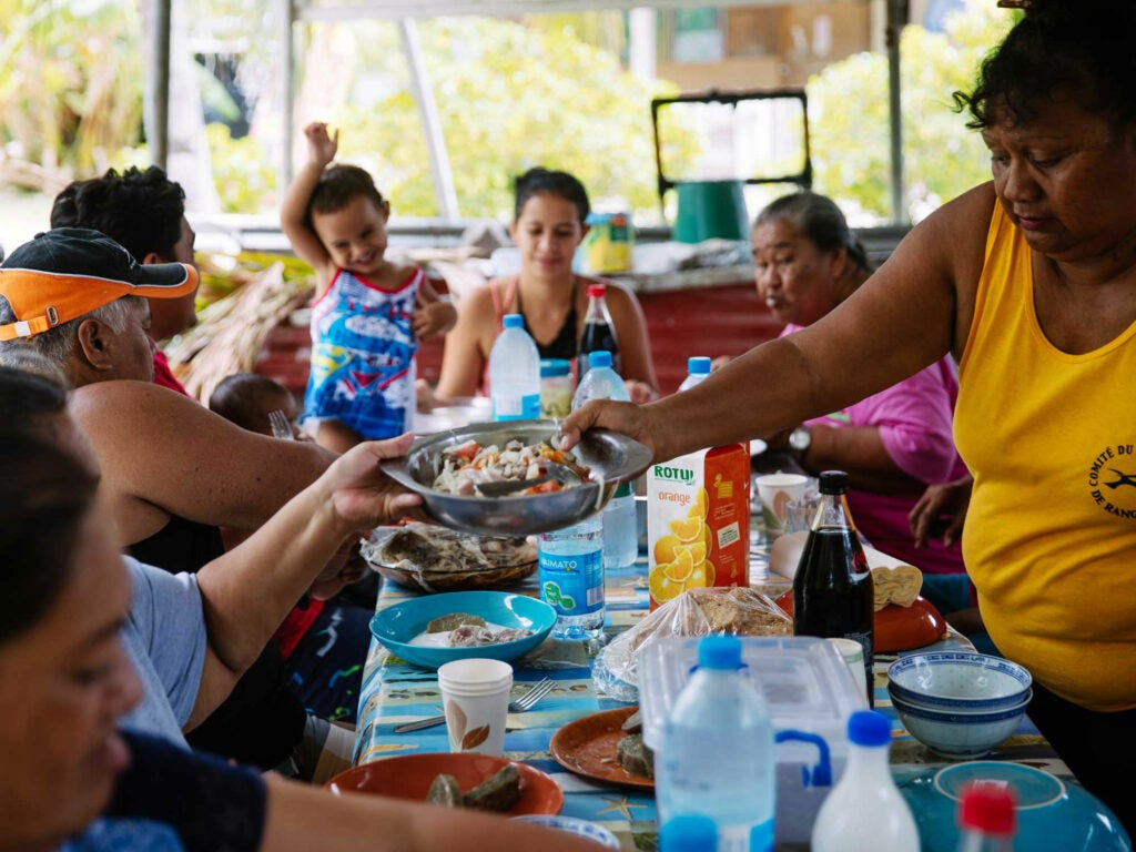 a Tahitian family passes dishes around a dinner table