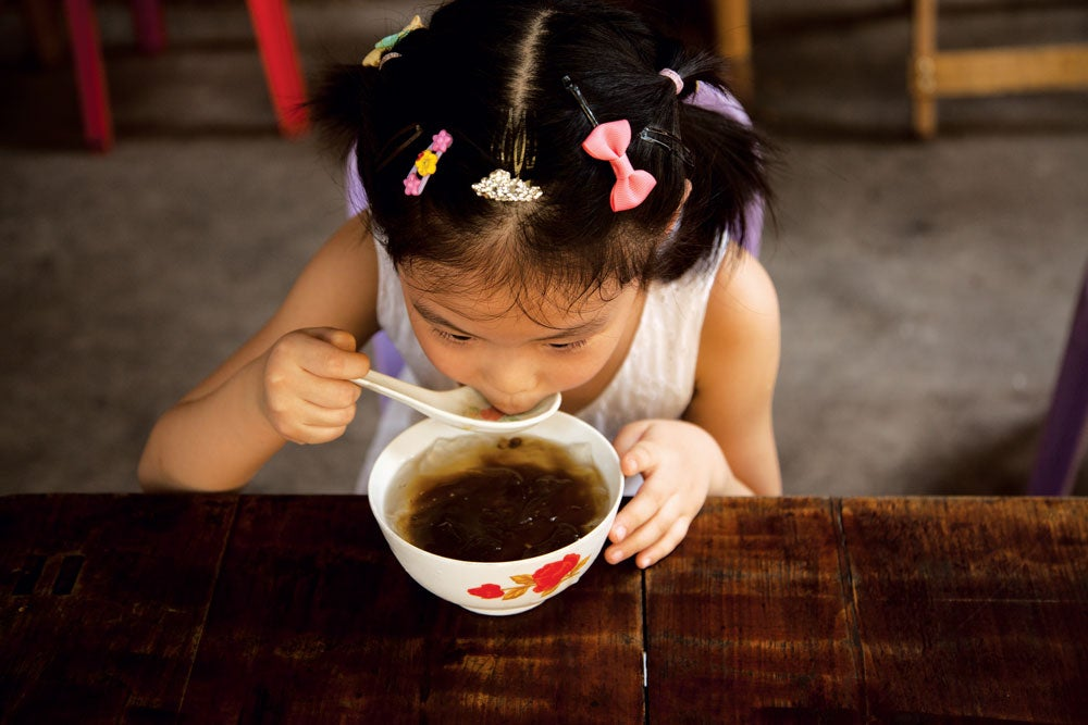 child eating spicy soup