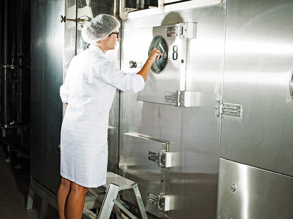 A quality-control assistant checks the flow of spaghetti during the machine's drying process.