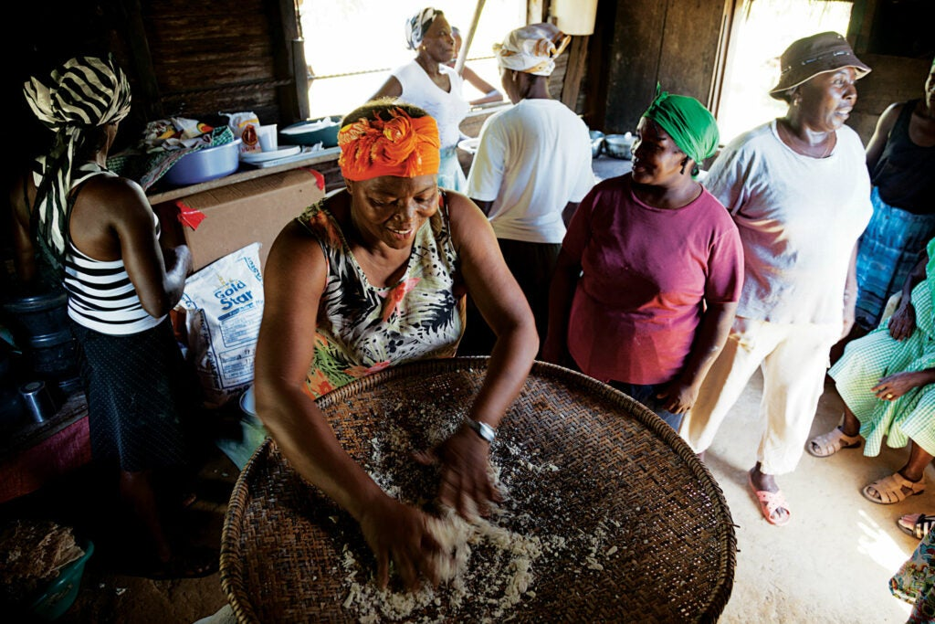 Camilla Leslie Crisanto Avila sifts cassava to make flour for bread while other Garifuna women look on