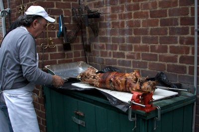 a man carves the Easter lamb in the backyard of their house in Queens, New York