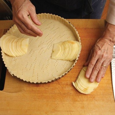 She returns the half to its flat side on the cutting board and covers it with her hand, pressing down until the mass of apple flattens into a neat row of overlapping slices