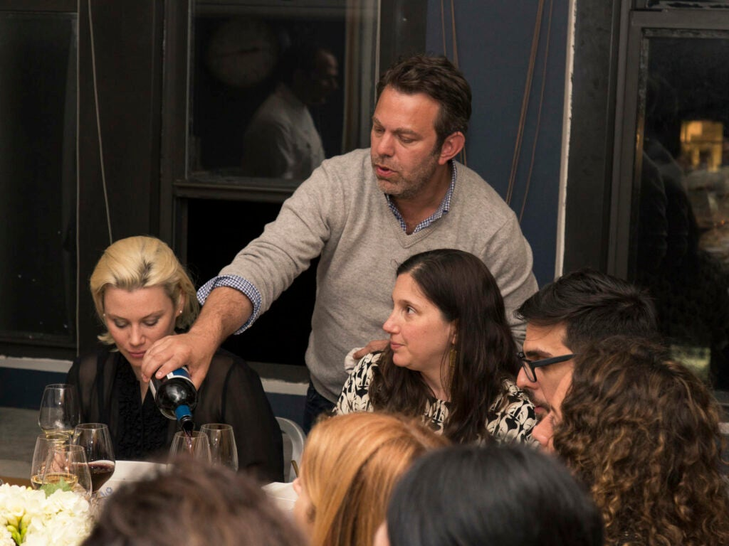 Editor-in-Chief Adam Sachs pours wine for Buzzfeed Food editor Sarah DiGregorio