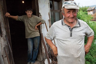 Gyuri Barabas, the local blacksmith in front of his workshop with his apprentice, in the village of Miklosvar