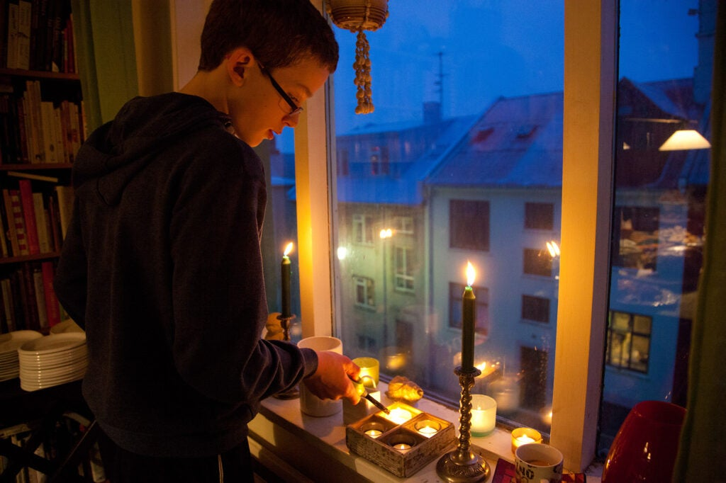 A boy lights candles in Iceland