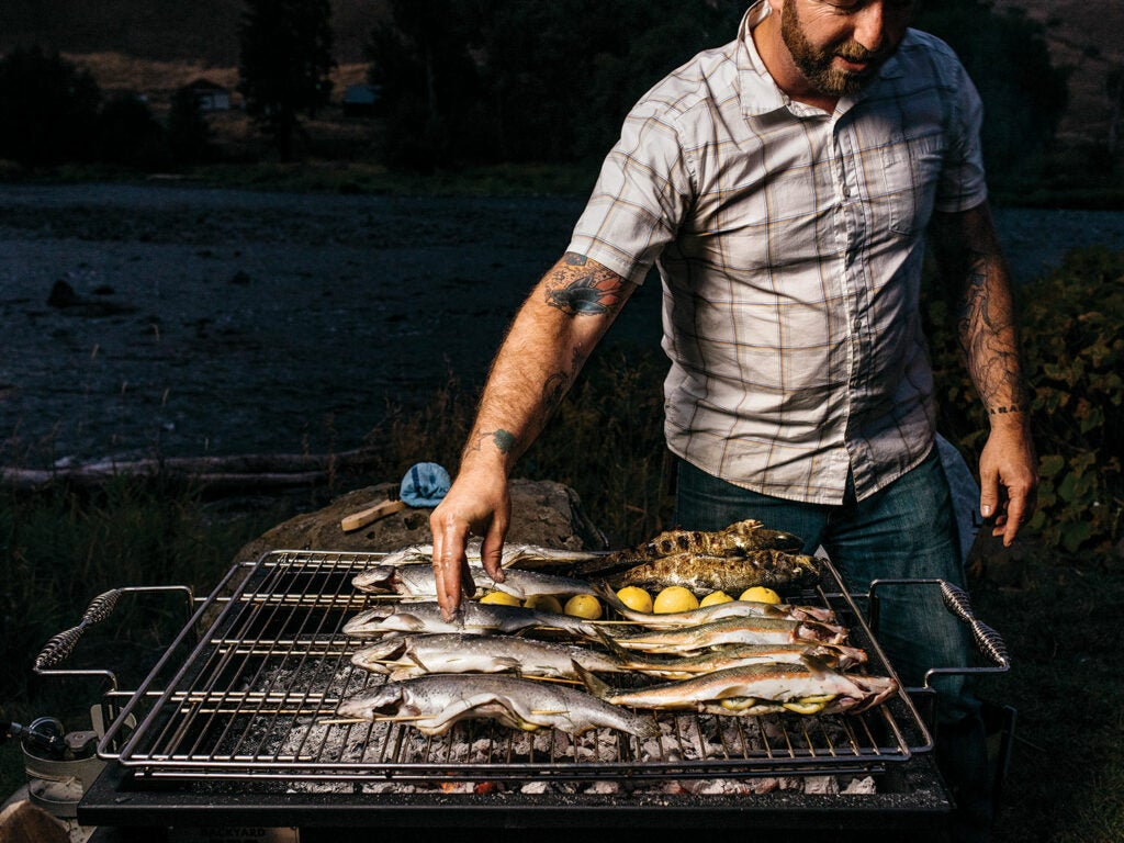 Elias Cairo tending to fish and lemons on grill