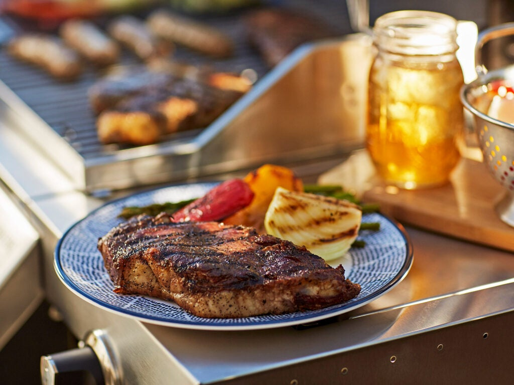 plate of grilled steak and vegetables on summer day