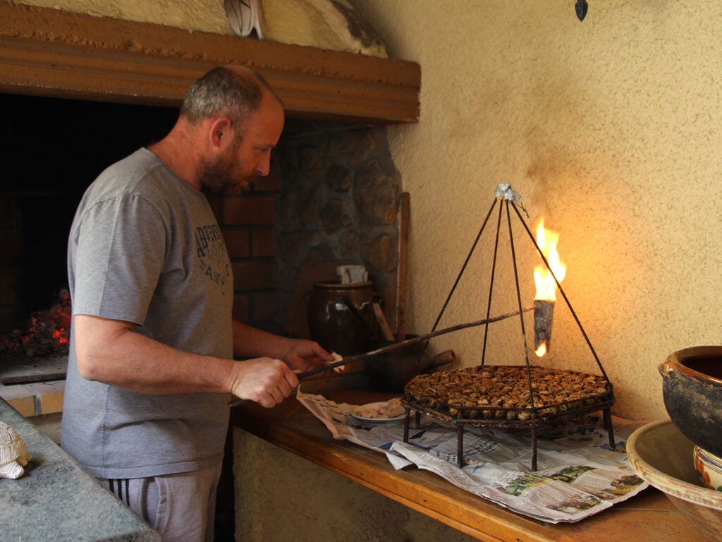 man drizzling flaming lard over snails