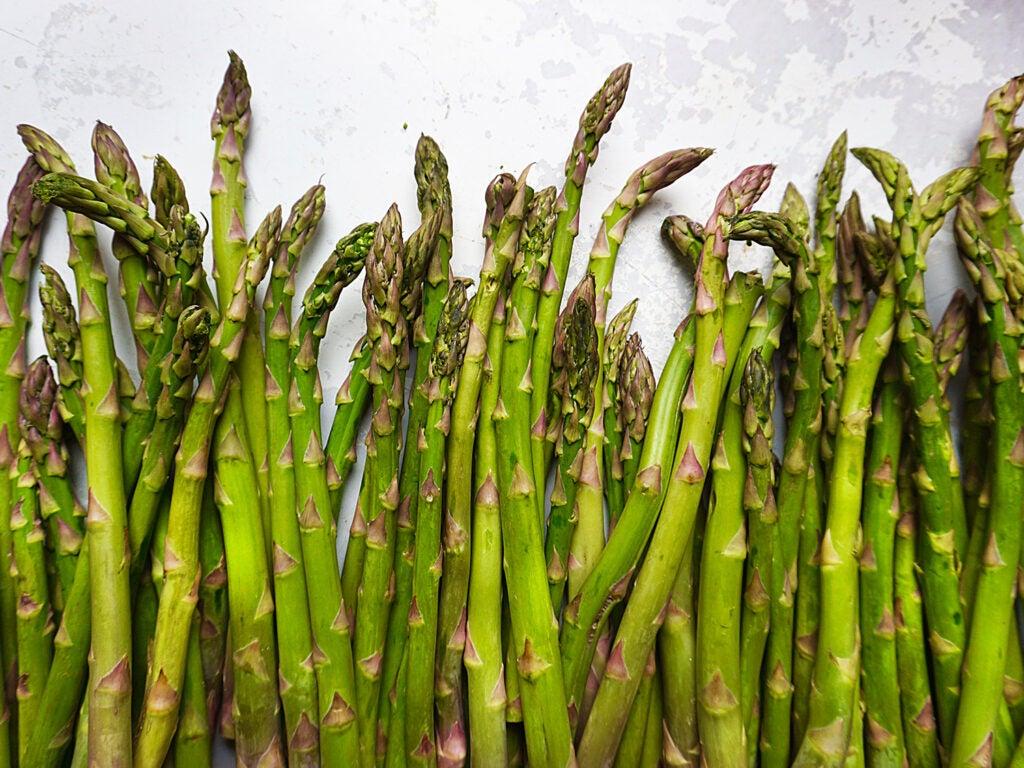 raw asparagus on white countertop