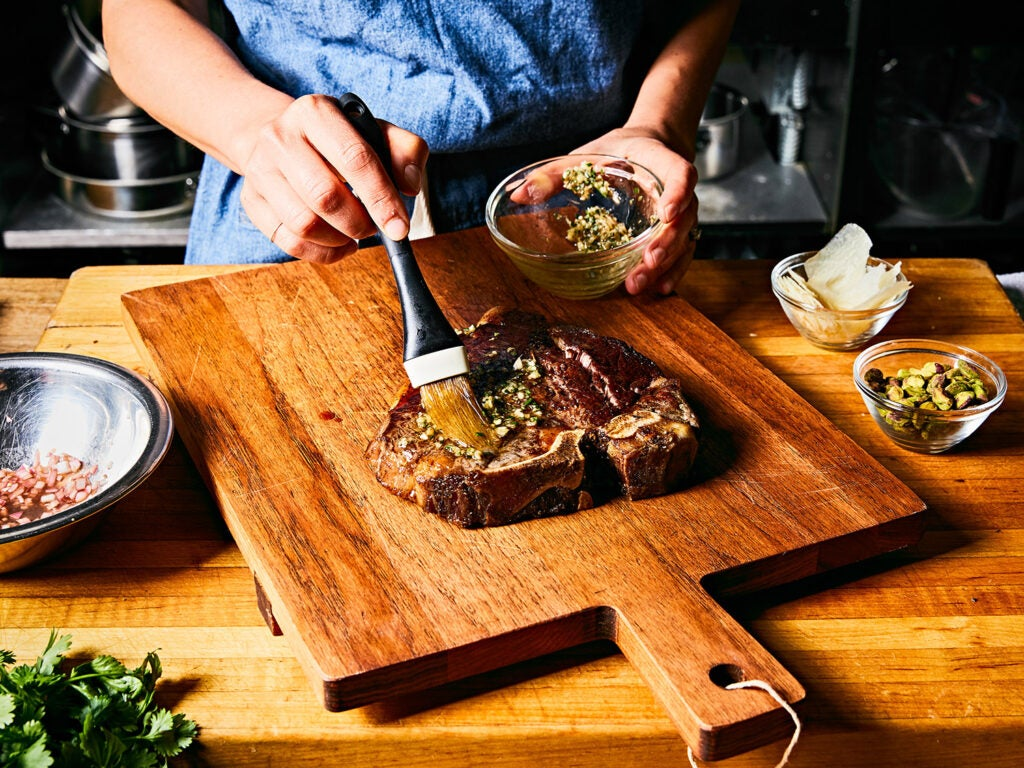 seasoning cooked steak on wooden cutting board