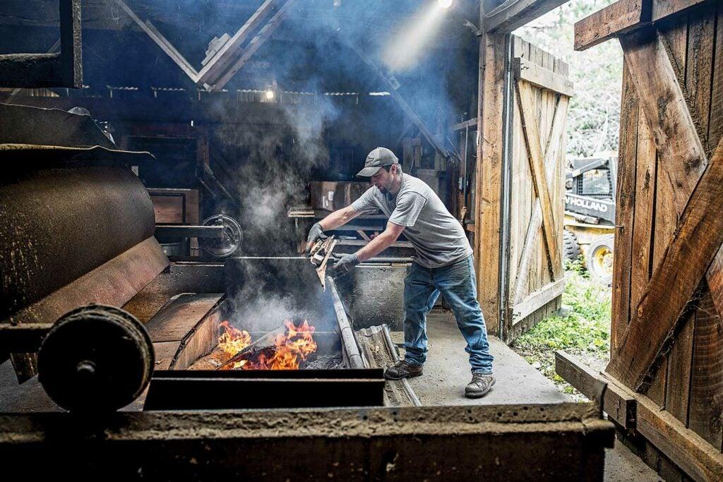 Aaron Dewandeler adds logs to his fire;