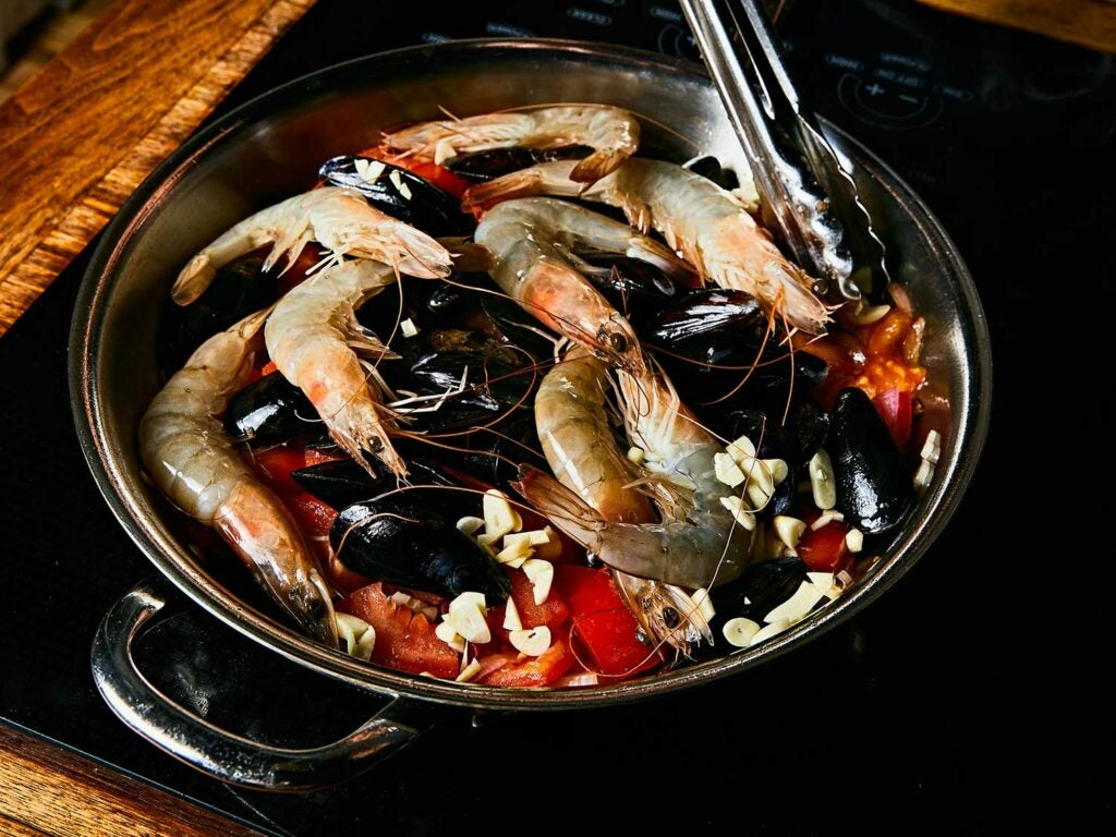 Seafood Pasta with Tomatoes, Chiles, and Mint in skillet.