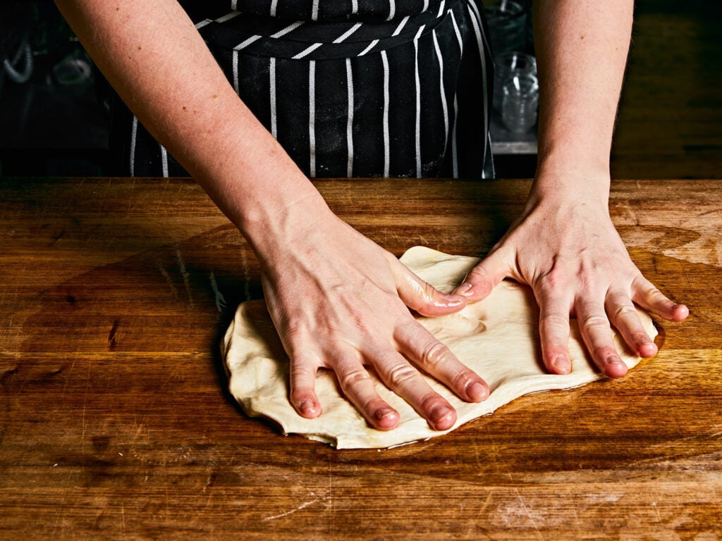 Spreading dough out by hand on an oiled board.