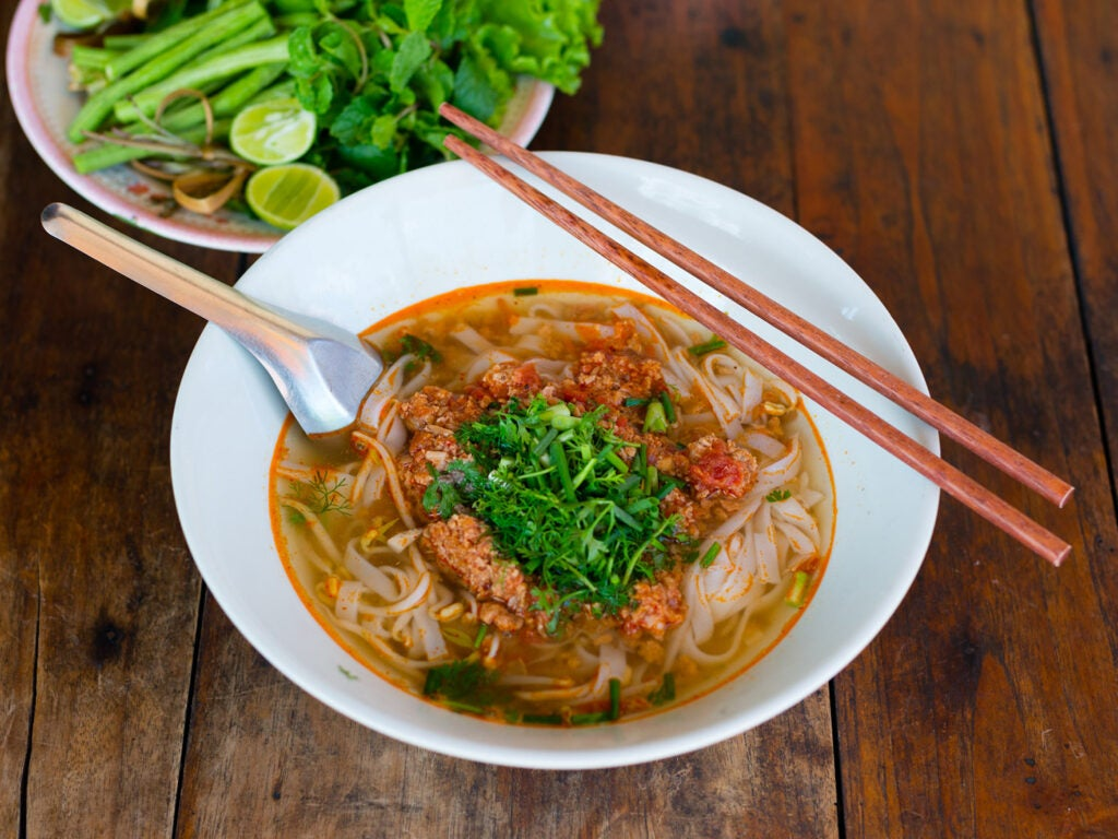 Khao soi in bowl with chopsticks.