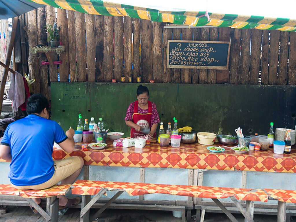 Man sits at vendor serving noodles in Laos.