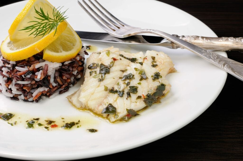 Slices of boiled fish with pesto and black, brown, and white rice on plate with silverware.