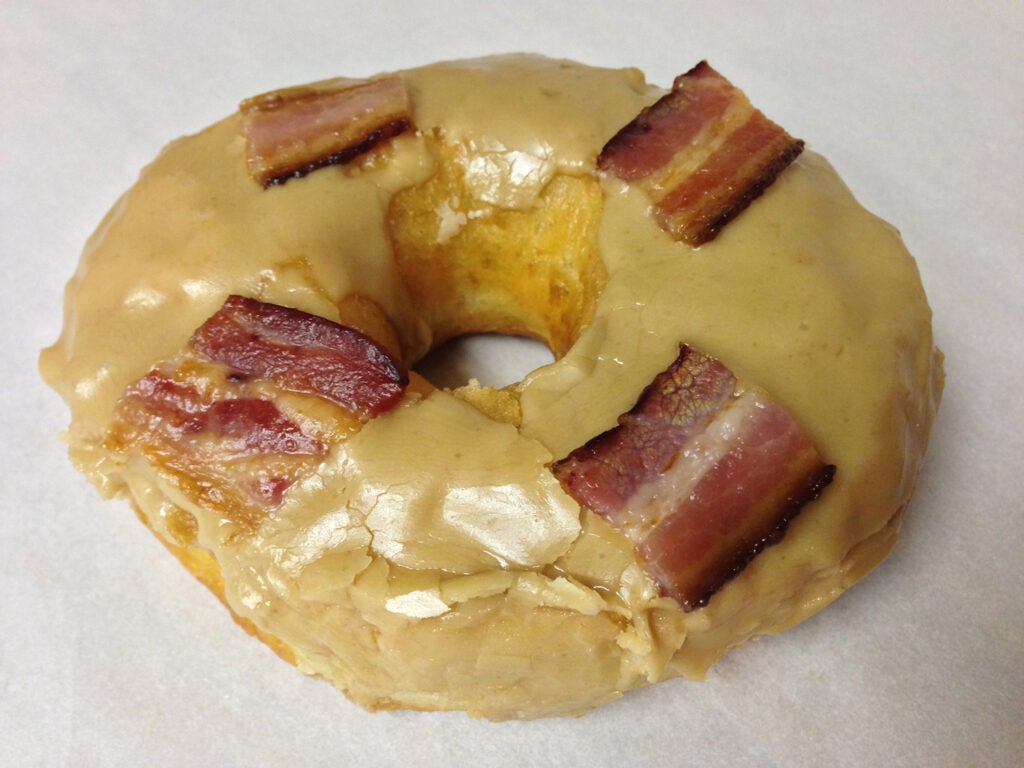 Maple bacon donut on white background.