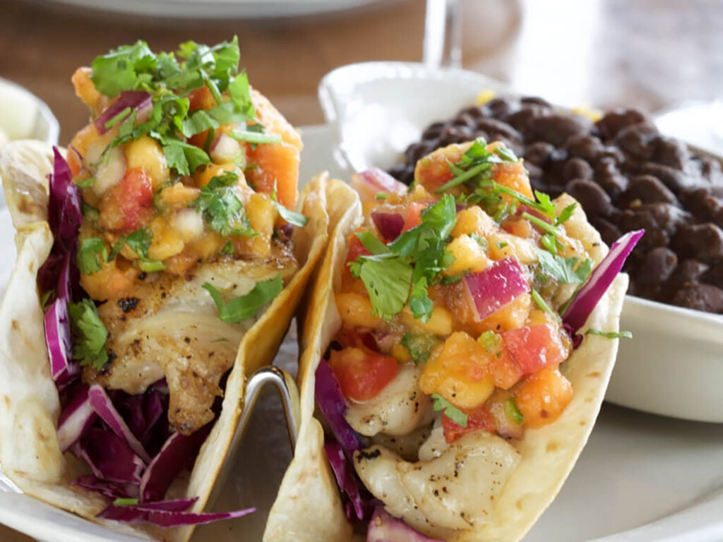 Pink shrimp tacos with rice and beans.