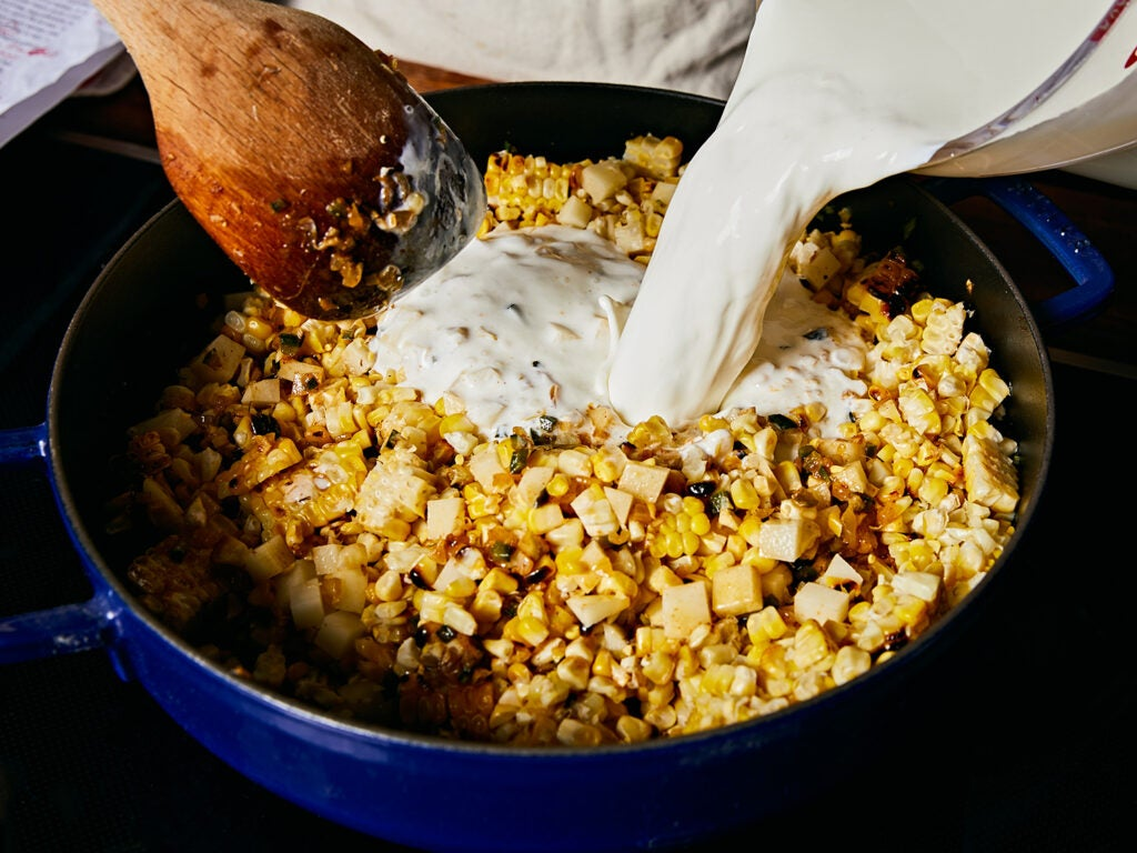 Pouring whole milk and heavy cream into grilled corn mixture.