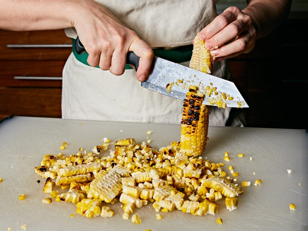 Cutting grilled corn kernels off the cob.