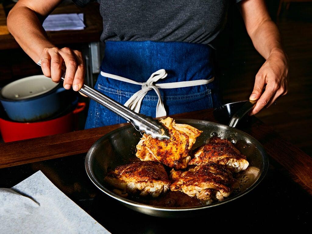 Searing chicken in skillet.