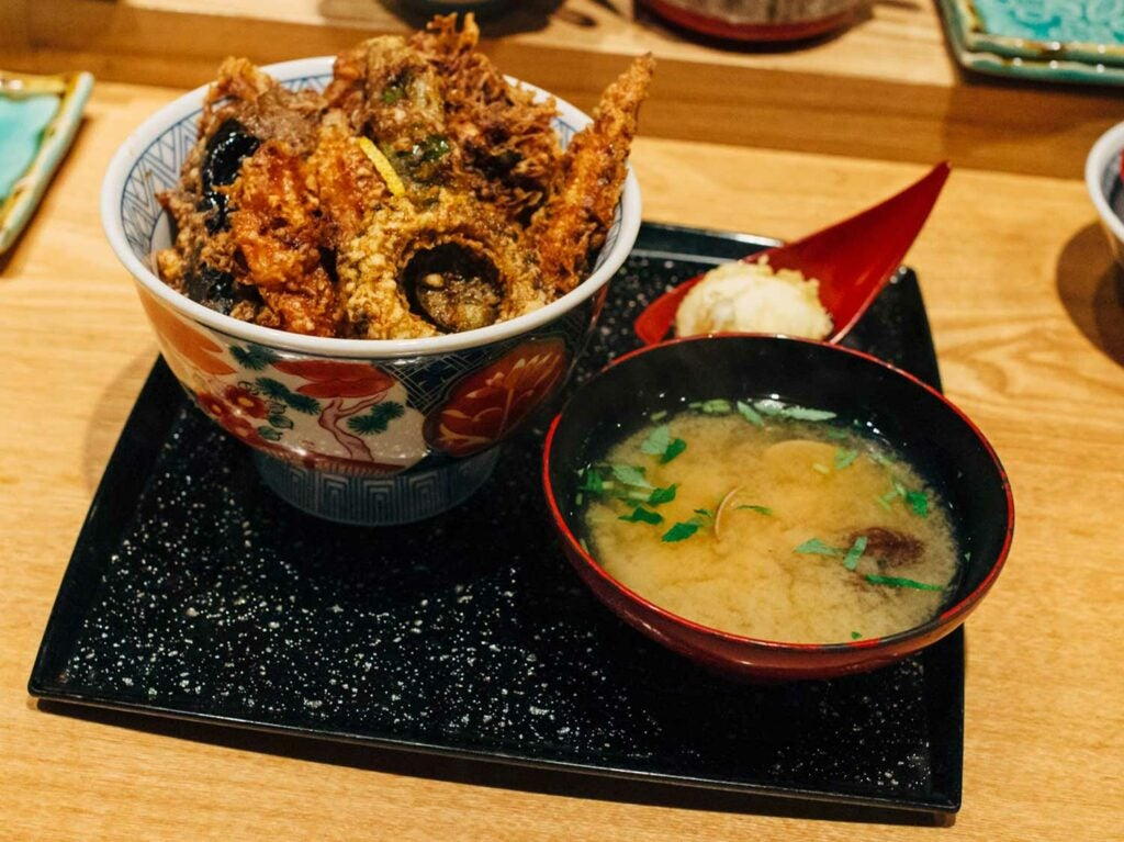 Isshin Kaneko's summer tendon with eggplant, bitter melon, and baby corn, and is served with clam miso soup and soft-boiled egg tempura.